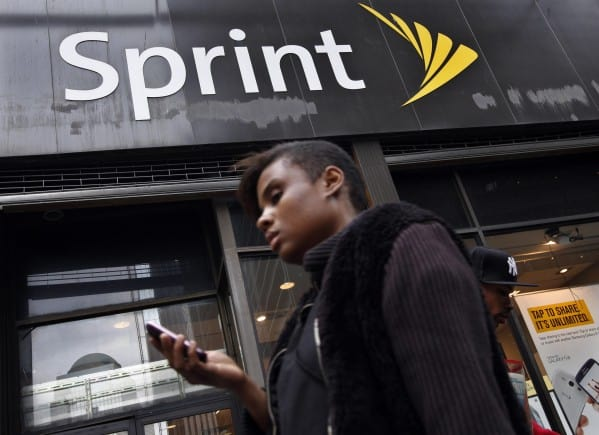 A woman uses her phone as she walks past a Sprint store in New York's financial district