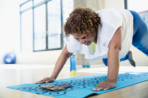 Happy woman looking at smart phone while exercising in yoga studio